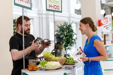 Специалист по технике Hurom Дмитрий консультирует посетителей стенда